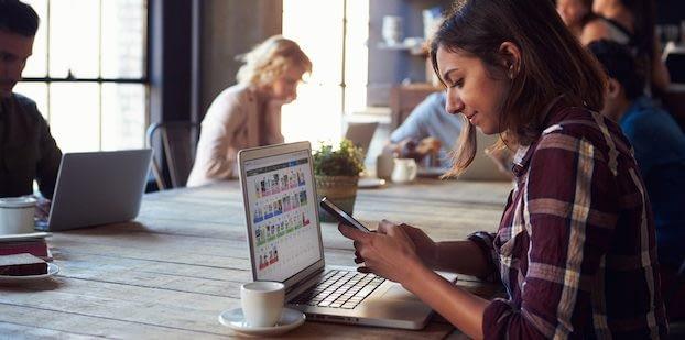 Frau im Café vor einem Laptop mit einem Mockup von Content-X.